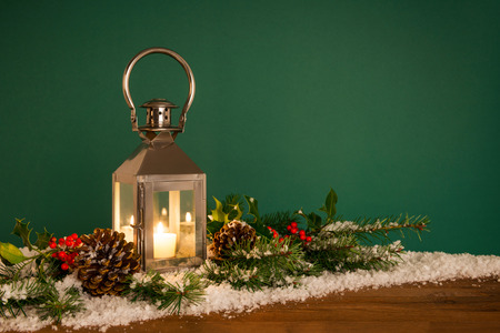 A Christmas lantern with a holly garland and snow against a green background. photo
