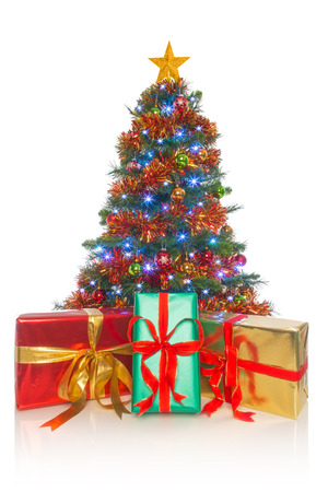 A decorated Christmas tree with gift wrapped presents in front isolated on a white background. photo
