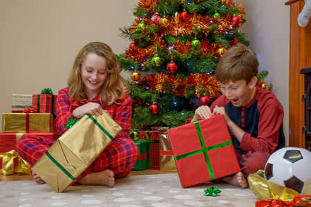 unwrapping: Two children, a boy and a girl, opening their presents on Christmas morning.