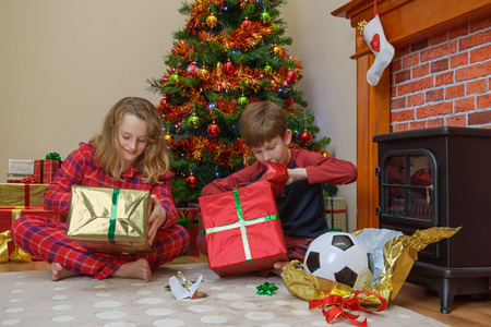 christmas morning: Two children, a boy and a girl, opening their presents on Christmas morning.