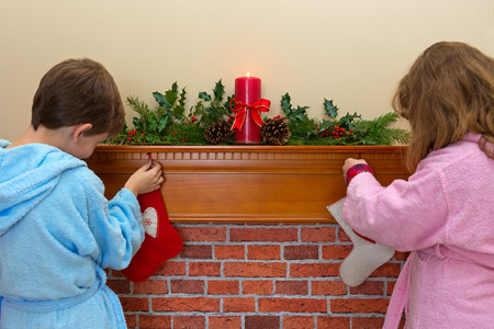 dressing gowns: A boy and a girl hanging their stockings over the fireplace on Christmas Eve