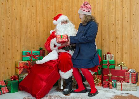 visiting: A girl in winter clothing visiting Santa in his grotto