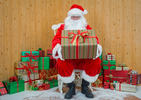 Santa Claus  Father Christmas sitting in his grotto holding a gift wrapped present for you. Stock Photo