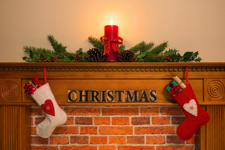 mantelpiece: Mantelpiece with red candle and fresh garland made from holly, two stockings full of gifts hanging over the fireplace with the word Christmas. Stock Photo