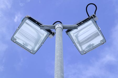 galvanised: Looking up at floodlights on a galvanised steel pole set against a bright blue sky Stock Photo