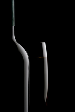 Wine bottle and wine glass on black background photo
