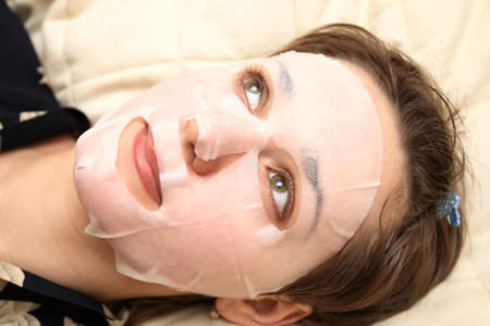 The girl lays  with a facial mask