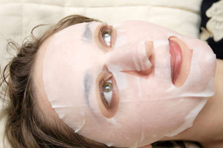 The woman recieving a face pack, close-up