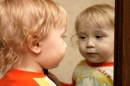 chłopięctwo: Chłopiec patrzy w lustro w domu Zdjęcie Seryjne