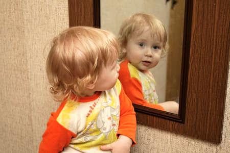 The boy looks in a mirror in hallway