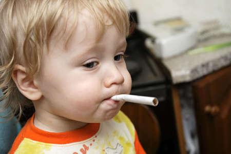 playful behaviour: The boy has stolen a cigarette at home