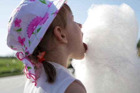 The girl licks candyfloss in the summer Stock Photo