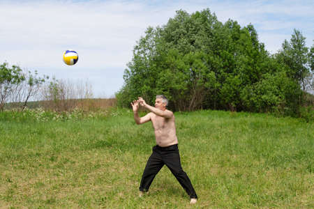The man plays with a ball outdoor in the summer Stock Photo - 1305234