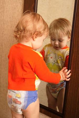 Boy in diaper looks in a mirror
