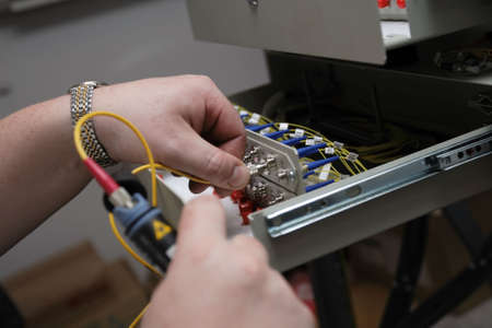 Engineer tests fiber-optic link by the reflectometer