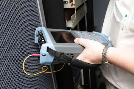 fiber cable: Engineer met reflectometer tests optische transmissie-lijn