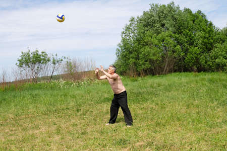 grassy plot: The man at grassy plot plays with a ball