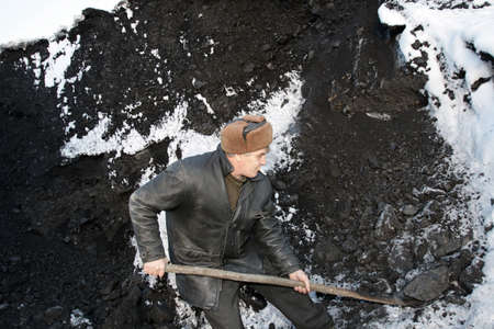 The working man handles the coal in winter photo