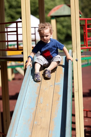 Toddler is sliding on a wooden slide at a playground photo