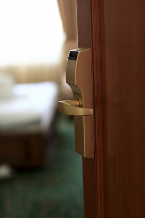 door lock: Open wooden door of the hotel room Stock Photo