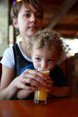 Toddler is drinking orange juice in the restaurant photo