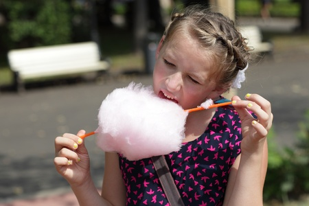 Girl licks cotton candy in the park photo