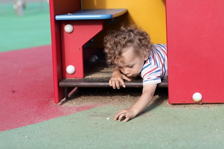Portrait of child in a toy house at outdoor playground photo