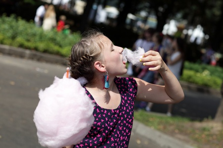 Girl is eating cotton candy in the park photo