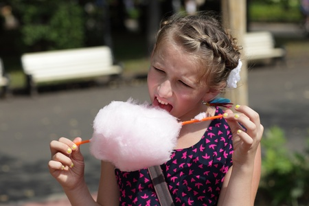 Kid licks cotton candy in the park photo