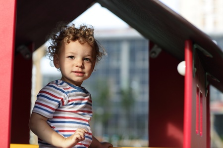 Portrait of todder in a toy house at outdoor playground photo