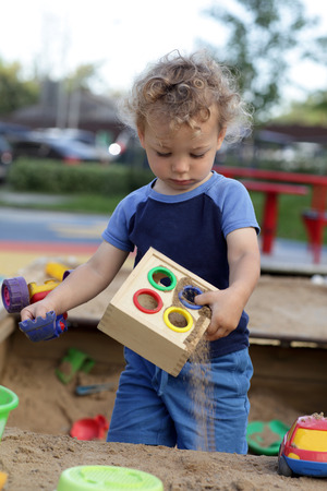Curly child is playing at sand box Stock Photo - 22349545