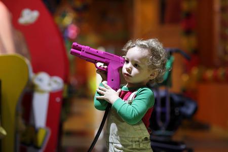pointing gun: Boy holding a gun at indoor playground