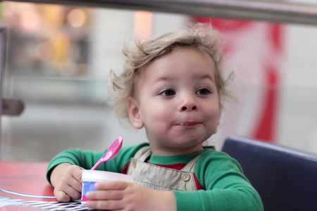 Toddler has ice cream in the cafe photo
