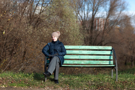Woman resting on bench at autumn park photo