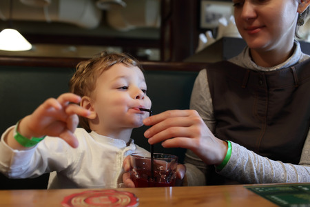 The child drinks juice in the restaurant photo