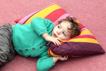 Child is lying on the carpet and colorful pillow photo