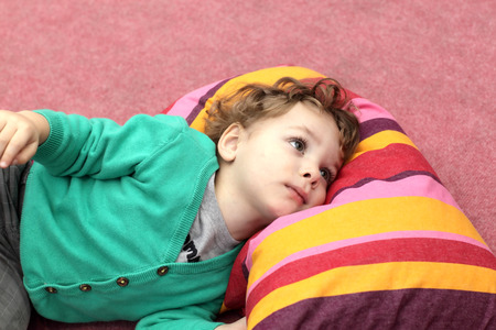 Kid is lying on the carpet and colorful pillow photo