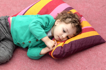 Boy is lying on the carpet and colorful pillow photo