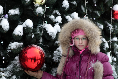 Girl is posing near the Christmas tree photo