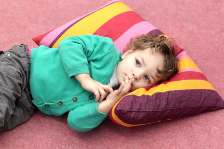 Toddler is lying on the carpet and colorful pillow photo