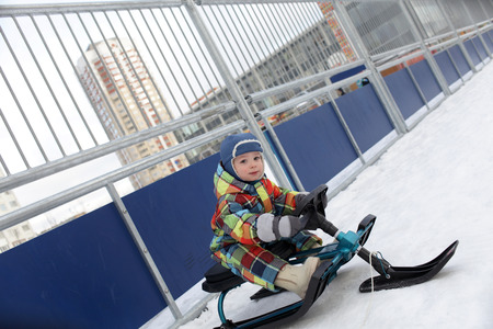 Kid on a snow scooter at a playground photo