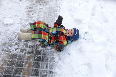 only one boy: Child lying in the snow on his back