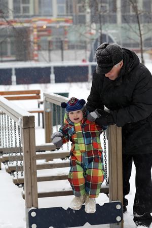 Grandfather and grandson playing at playground in winter Stock Photo - 24734729