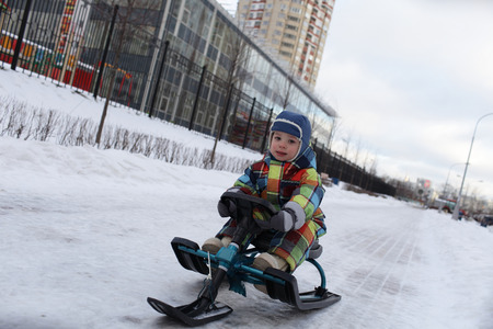 Toddler slides on snow scooter at a park photo