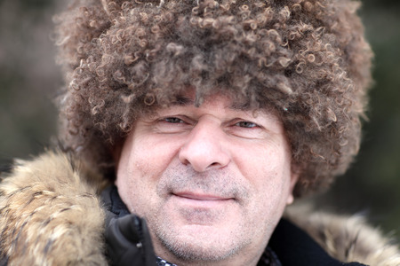 papakha: Man posing in brown caucasian hat in winter Stock Photo