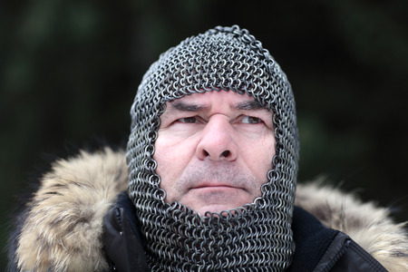 Mature man posing in armor outdoor in winter