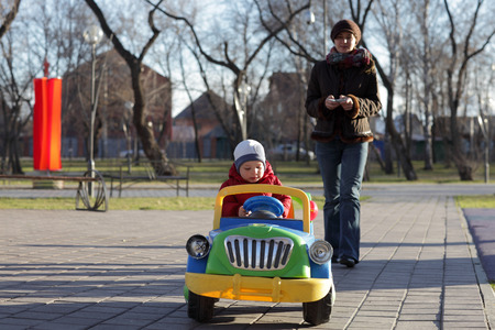 remote controls: Mother controls the car with her son using remote control