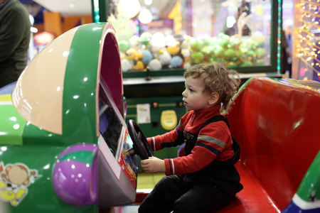 Child driving car toy at an amusement park photo