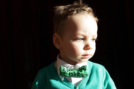 hair tie: Boy in a green cardigan with white shirt and bow tie  Stock Photo