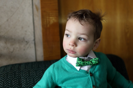 hair tie: Child in a green cardigan with white shirt and bow tie